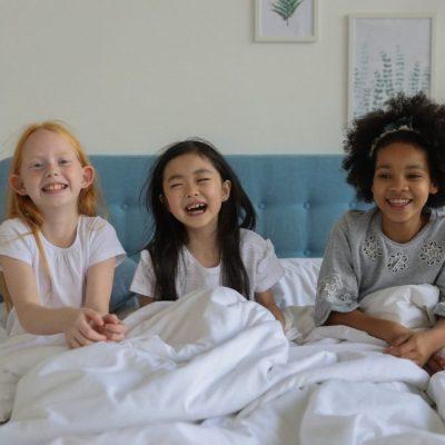 https://www.pexels.com/fr-fr/photo/heureux-diverses-copines-au-lit-sous-une-couverture-5063284/